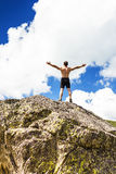 Young man standing on top of a cliff with arms raised Stock Photo