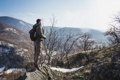 Young man standing on top of cliff in winter mountains holding a. Camera and enjoying view. Hiker with backpack standing on a cliffs edge on the top of mountain Royalty Free Stock Photography
