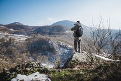 Young man standing on top of cliff in winter mountains holding a royalty free stock photo