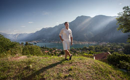 Young man standing on top of high mountain at sunny day. Handsome young man standing on top of high mountain at sunny day Stock Photos