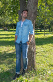 Young man standing at tree in park in summer Royalty Free Stock Photos