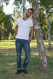 Young man standing at tree in park in summer Royalty Free Stock Photography