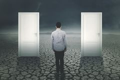 Young man standing with two doors Stock Photo