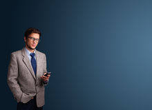 Young man standing and typing on her phone with copy space Stock Images