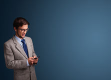 Young man standing and typing on her phone with copy space Stock Photos