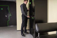 Young man standing unlocking a cabinet. Young man standing unlocking a black metal filing cabinet in a waiting room with a key, side view Stock Images