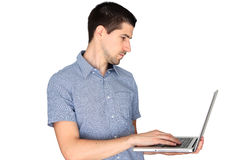 Young man standing and using laptop Stock Image