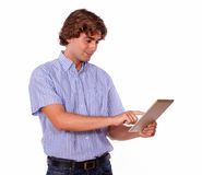 Young man standing and using on tablet pc. Royalty Free Stock Image