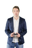 Young man standing, with videogame joypad in his hands. Young man playing videogames with joypad or joystick, standing and isolated on white Stock Photography