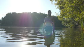 Young man standing in water at summertime and relaxing. Guy rest at river stock video