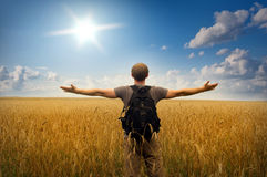 Young man standing on a wheat field. On sunset sky background stock photography