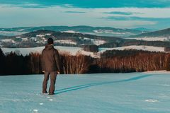 Young man standing in winter czech landscape looking to valley.  stock photo