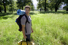 Young man standing in woodland clearing on camping trip, carrying rucksack, tent bag and sleeping bag, smiling, side view Royalty Free Stock Photography