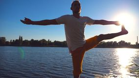 Young man standing at yoga pose on wooden jetty at lake. Athlete balancing on one leg at nature. Sporty guy doing. Stretch exercise outdoor. Concept of healthy stock video