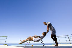 Young man standing by young woman lying on deck chair by sea, smiling at each other, side view Royalty Free Stock Photography