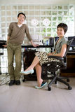 Young man standing by young woman sitting by desk in office, smiling, portrait Stock Images