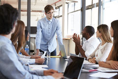 Young man stands addressing colleagues at business meeting Royalty Free Stock Images
