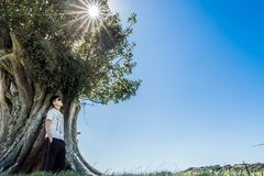 Peaceful image of young man stands against a tree stock photography