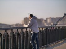 Young man stands alone on a bridge on a sunny day, rear view stock image