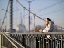 Young man stands alone on a bridge on a sunny day, rear view, copyspace stock images
