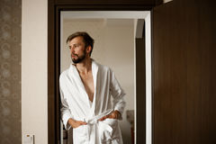 Young man stands in bathrobe and looks away. Young man in white bathrobe stands in doorway of hotel and looks away royalty free stock photography