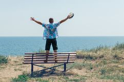A young man stands on a bench with his arms raised and enjoys the view of the sea.  royalty free stock image