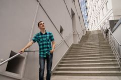 The young man is standing on the big stairs royalty free stock image