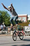 Young Man Stands On Bike Handlebars Practicing For BMX Competiti Stock Photo
