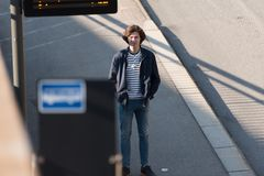 Young man stands in a bus stop. And waiting for a bus stock photos