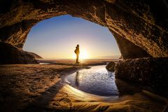 Man deep thinking inside wharariki beach cave in New Zealand stock photo