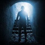 Young man stands in dark stone tunnel, blue toned Stock Images