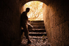 Young man stands in dark stone tunnel Stock Photography