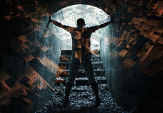 Young man stands in dark tunnel with glowing end Royalty Free Stock Images