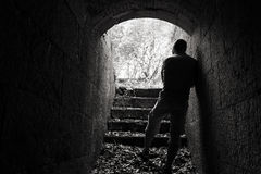 Young man stands in dark tunnel with glowing end Stock Images