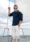 Young man stands on deck of a yacht under a sail Stock Images