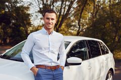 Man stands in front of his new car stock photography