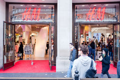 H&M store in London. A young man stands in front of the newly remodelled  H&M flagship store in Oxford Circus in London on March 14th, 2013 Royalty Free Stock Image