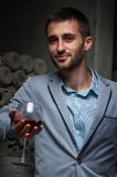Young man stands with glass of wine. Handsome man looking at the camera with red glass of wine during a wine tasting Royalty Free Stock Image