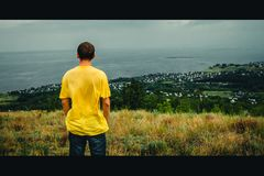 A young man stands with his back against the background of the village royalty free stock images