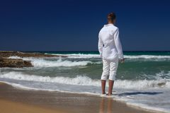 A young man stands with his back on the beach Royalty Free Stock Photos