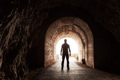 Young Man Stands In Dark Concrete Tunnel