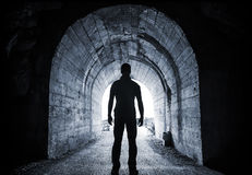 Young Man Stands In Dark Tunnel