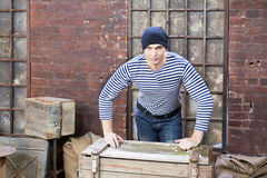 Young man stands, leaning his hands on wooden chest. Young man in striped vest stands, leaning his hands on wooden chest Royalty Free Stock Photography