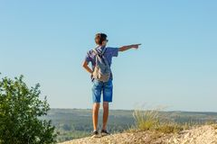 A young man stands on a mountain and looks into the distance showing a hand direction royalty free stock images
