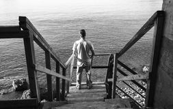 Young man stands on old stairway. Young man stands on old wooden stairway going down to the sea coast, black and white photo Stock Photos