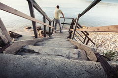 Young man stands on old wooden stairway Stock Photos
