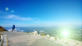 A young man stands on a path at the mausoleum on Lovcen in Montenegro. Panoramic views of mountains and fields Royalty Free Stock Photos
