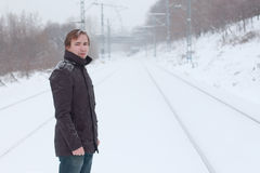 Young man stands on railway and looks away at winter Stock Image