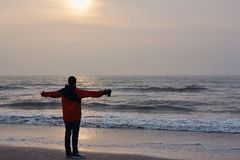 Young man stands on the shore of the North sea and looks into the distance stock photos