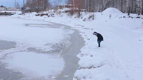 Young man stands on snow-covered Bank of frozen river then sit on snow. Young man in black jacket with fur hood stands on snow-covered Bank of frozen river then stock video footage